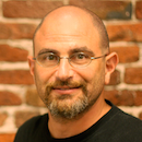 Photo of Ken Mayer, with the standard SF-SOMA-start-up brick wall background